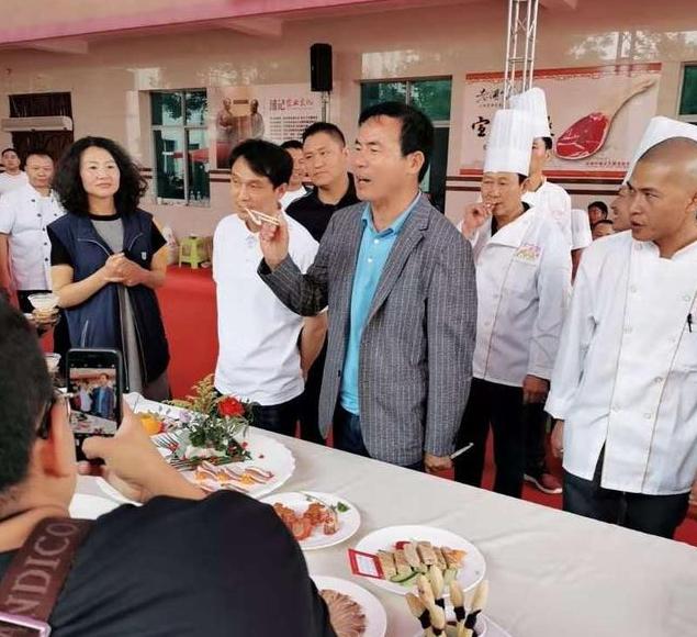 图为,云南宣威市浦记火腿食品有限公司董事长浦恩勇点评参赛作品。